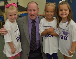Superintendent Rust with Kindergarten students receiving 2029 t-shirts